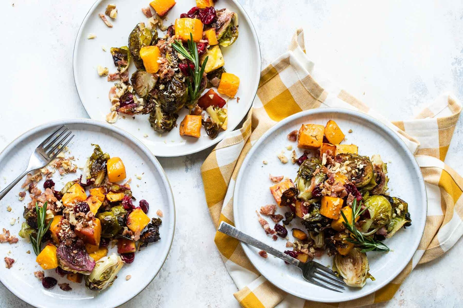 Three servings of harvest roasted vegetables on separate white plates.
