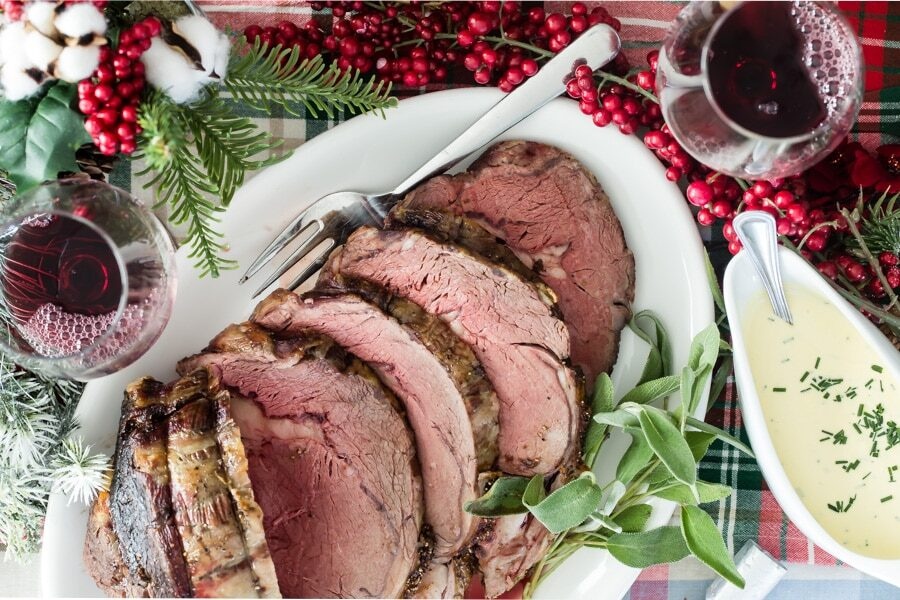 A platter of sliced prime rib on a Christmas-themed table.