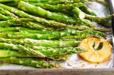 A baking sheet full of roasted asparagus with lemons.
