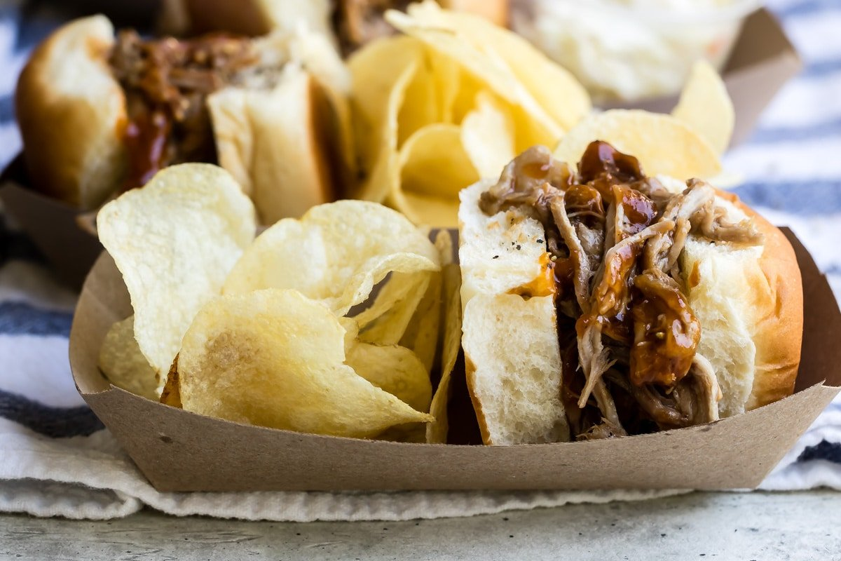 A paper food boat with a pulled pork sandwich and potato chips.
