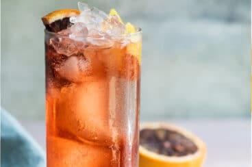 An Americano in a high ball glass with a blood orange garnish.