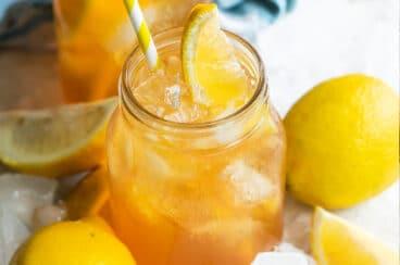 An arnold palmer in a mason jar with a lemon wedge garnish.