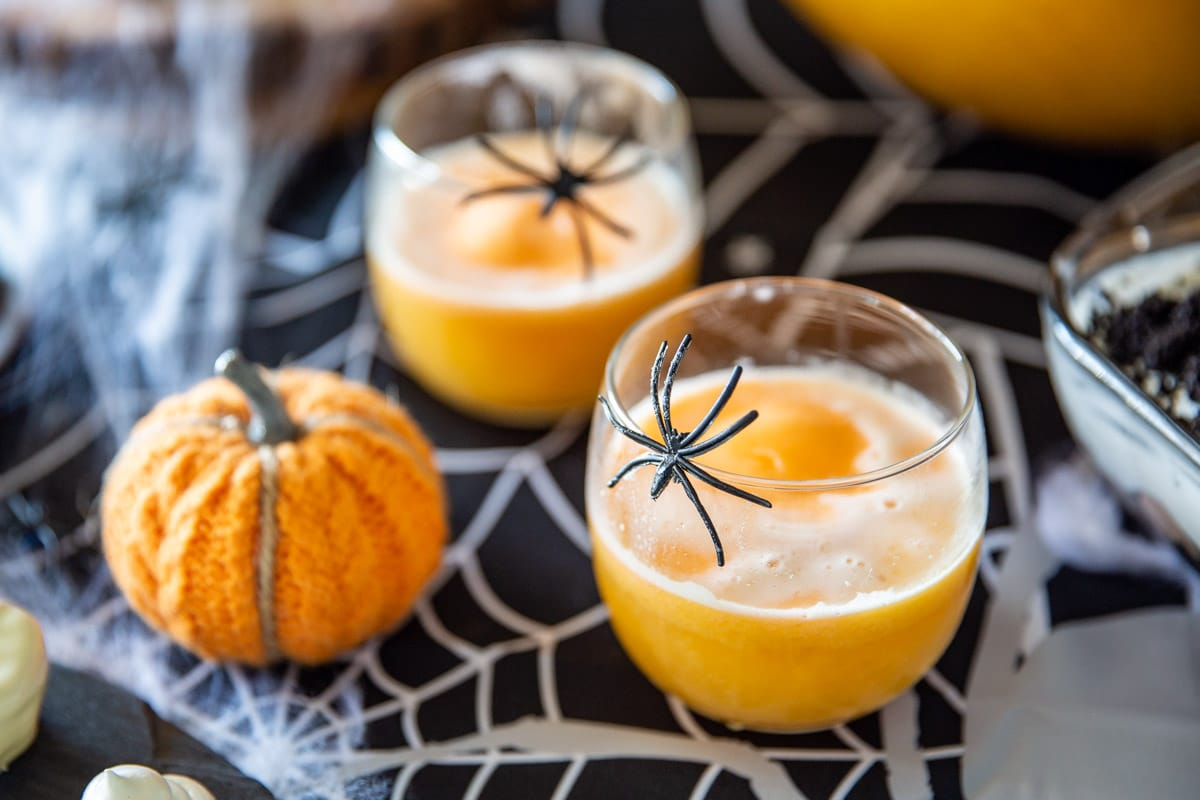 Fruit punch in glasses with plastic spiders on the side for Halloween.