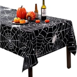 A halloween table cloth on a table with decorative pumpkins.