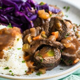 A plate with rouladen, braised red cabbage, and mashed potatoes.